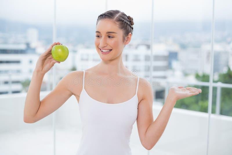 Усмехаясь sporty брюнет держа зеленое здоровое яблоко стоковое фото rf