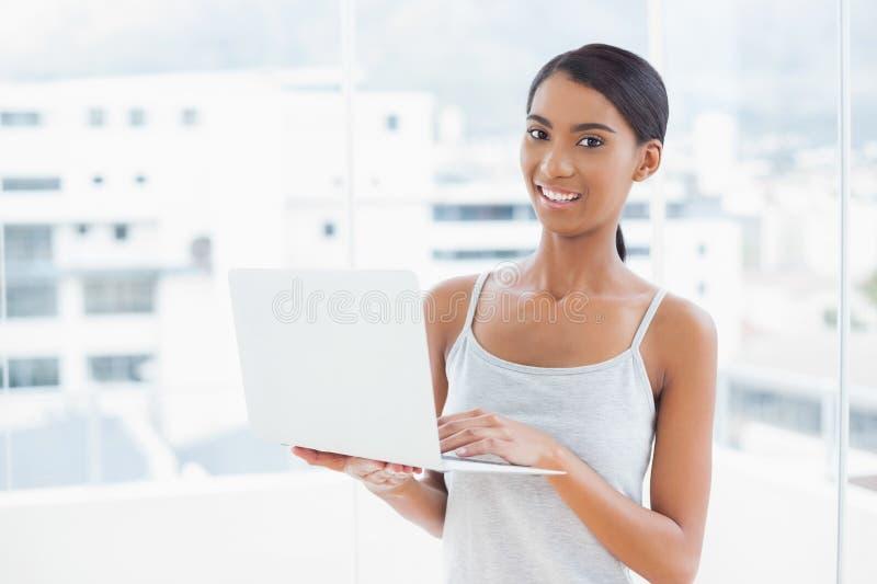 Download Усмехаясь Sporty модель используя ее компьтер-книжку Стоковое Фото - изображение насчитывающей волосы, связано: 33739506