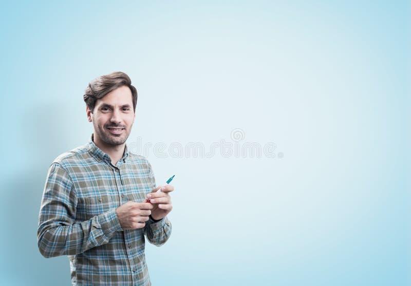 Усмехаясь startup основатель с отметкой, голубая стена стоковое изображение