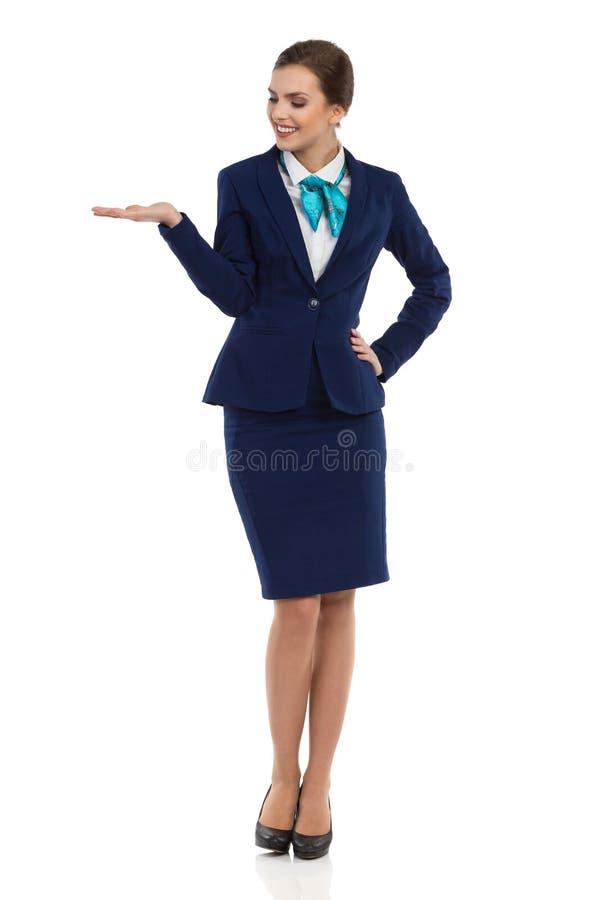 Усмехаясь Stewardess представляя и наблюдать стоковое изображение rf