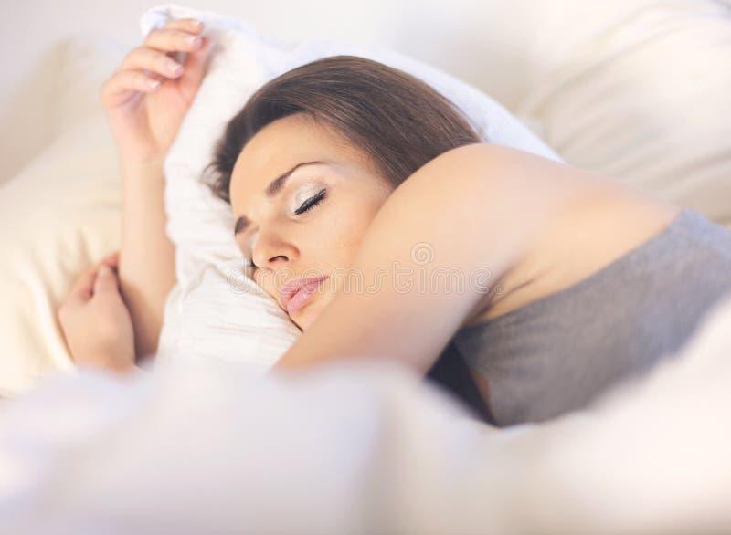 Уснувшая женщина лежа на кровати стоковое фото rf