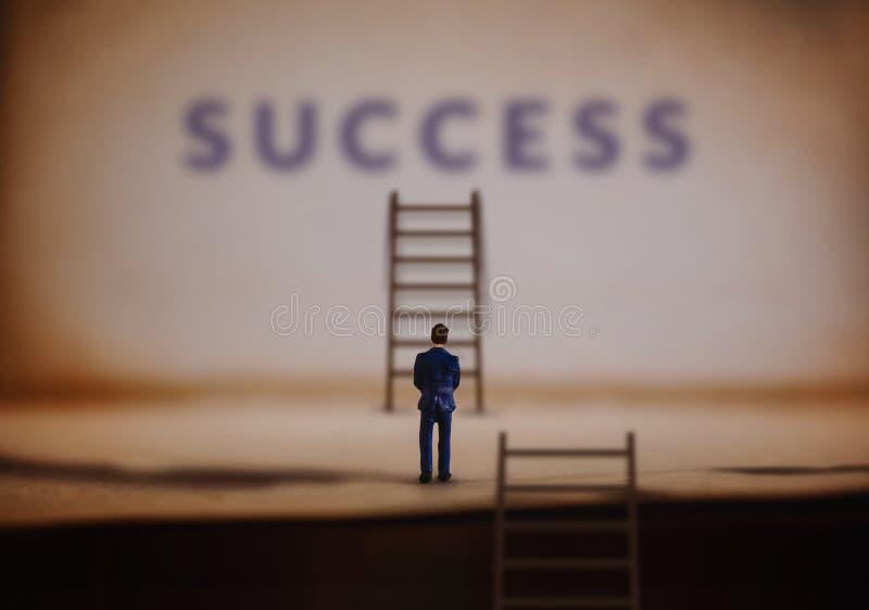 Успех в жизни и деле или личной концепции таланта Молодой миниатюрный бизнесмен стоя перед лестницей успеха лестницы стоковые изображения rf