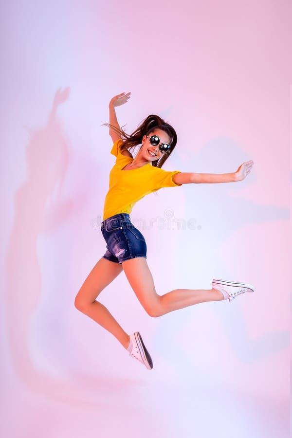 Успех, мечта, концепция жизни femenine girlish Excited модель дамы брюнет скачет вверх, нося вскользь одежды, белые стоковая фотография