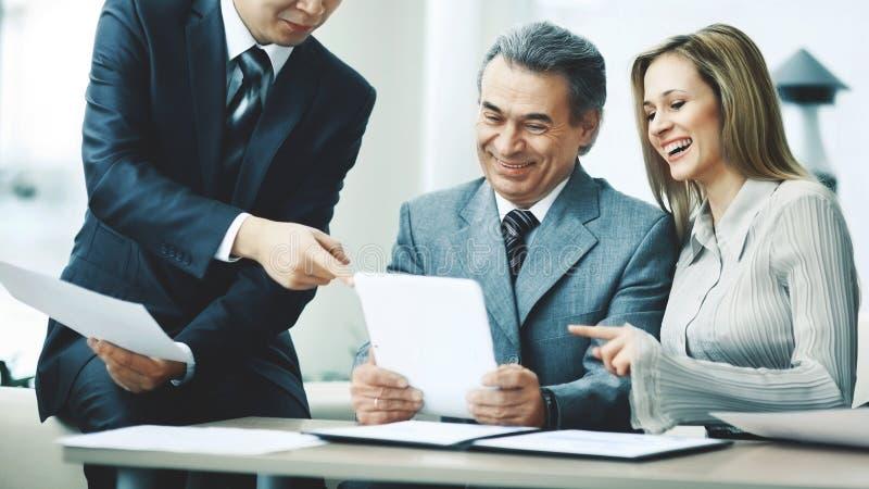 Успешная бизнес-группа обсуждает рабочий план используя таблетку стоковое изображение rf
