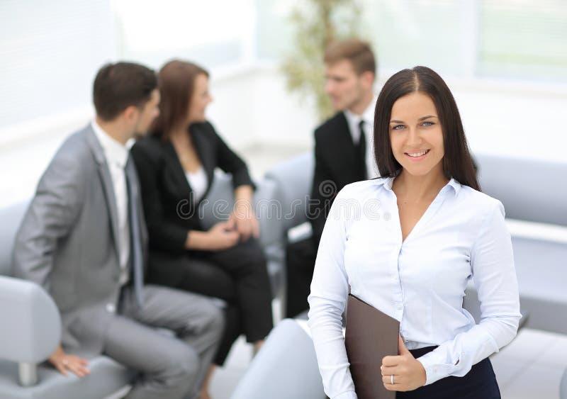 Успешная бизнес-леди стоя с ее штатом в предпосылке стоковое изображение