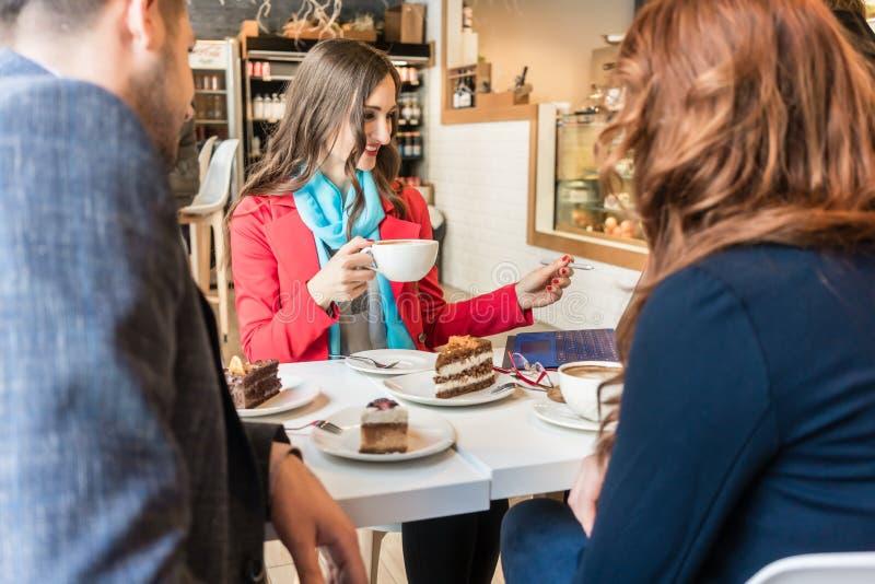 Успешная бизнес-леди используя компьтер-книжку пока наслаждающся чашкой кофе стоковое фото rf