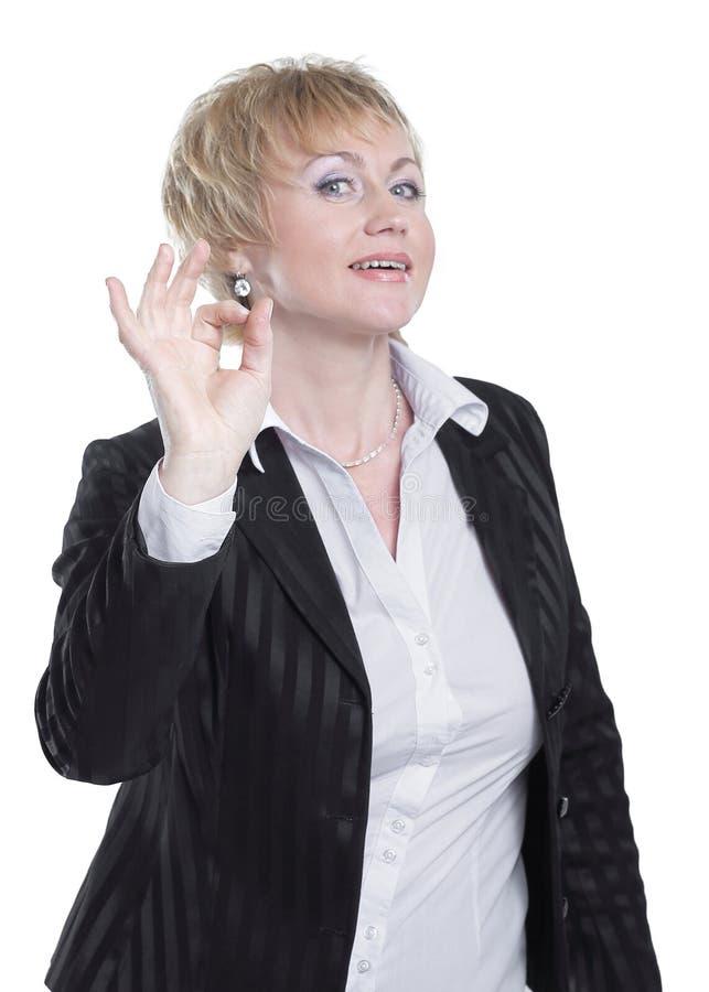 Успешная бизнес-леди показывая ОДОБРЕННЫЙ знак Изолировано на белизне стоковое изображение rf