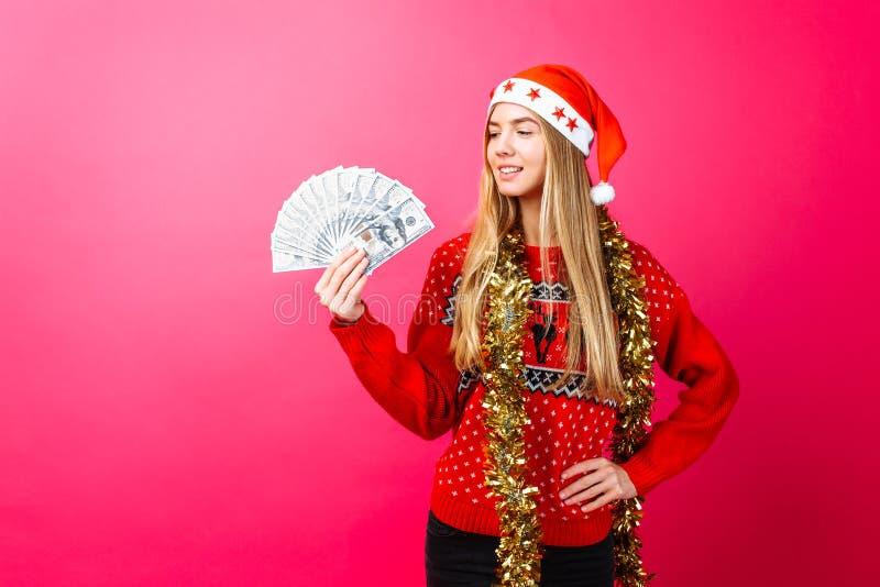 Успешная девушка в красном свитере и шляпе Санта держа деньги на красной предпосылке стоковые изображения