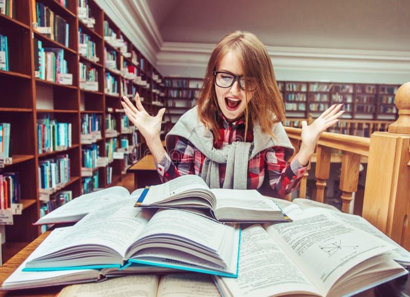 Успешная девушка изучая крепко в библиотеке стоковое изображение