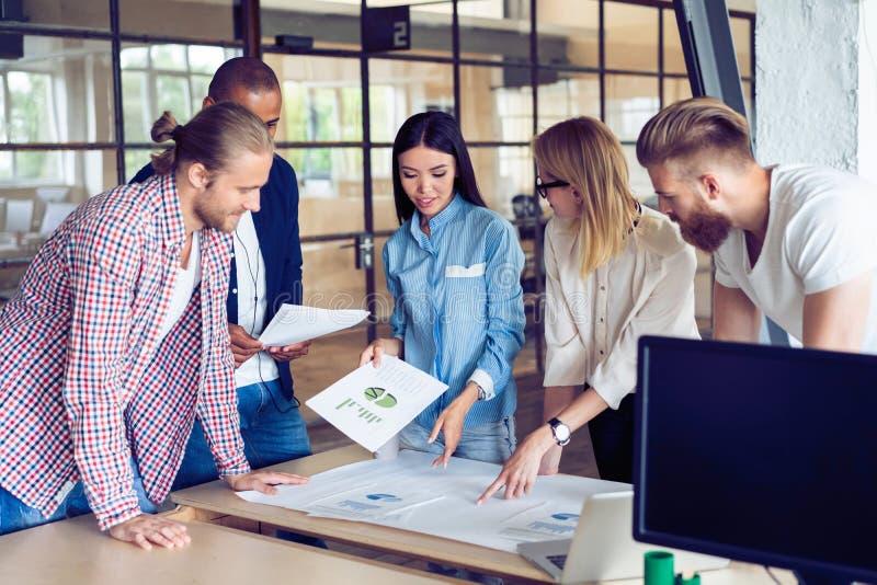 Успешная команда Группа в составе молодые бизнесмены работая и связывая совместно в творческом офисе стоковая фотография