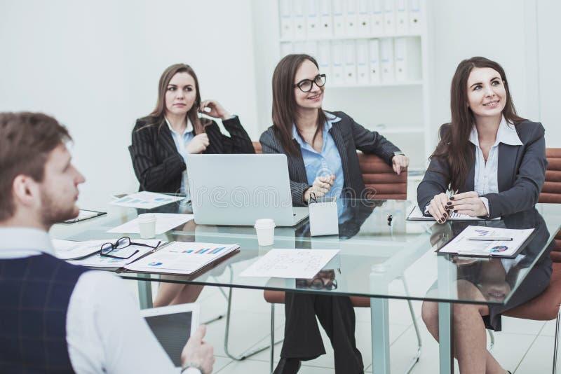 Успешная команда дела на мастерской слушая к боссу стоковое фото rf