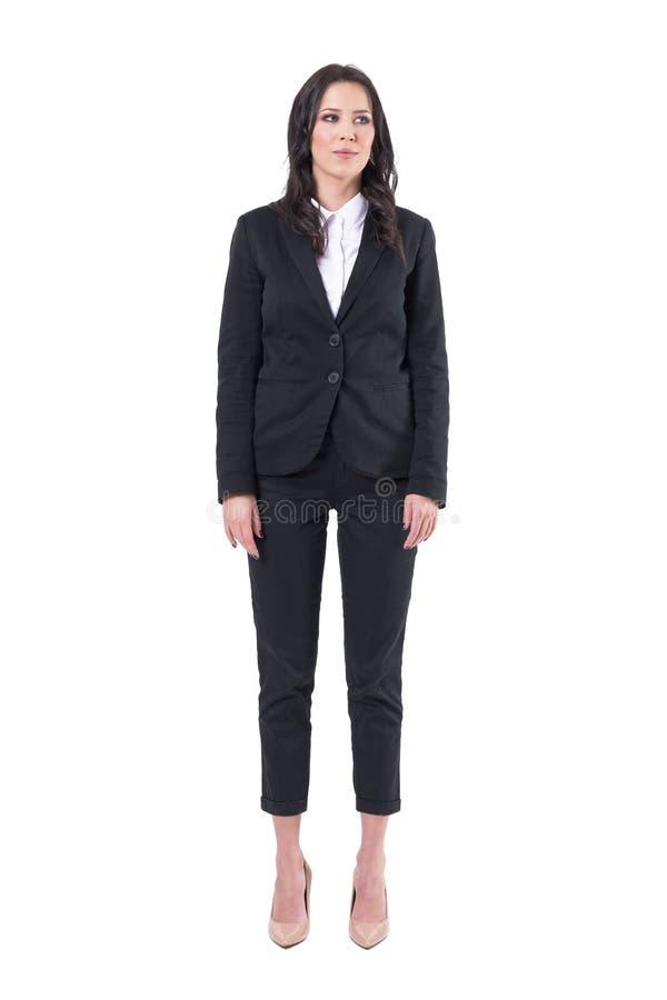 Успешная молодая милая бизнес-леди в черном положении костюма с оружиями вниз со смотреть прочь стоковая фотография rf