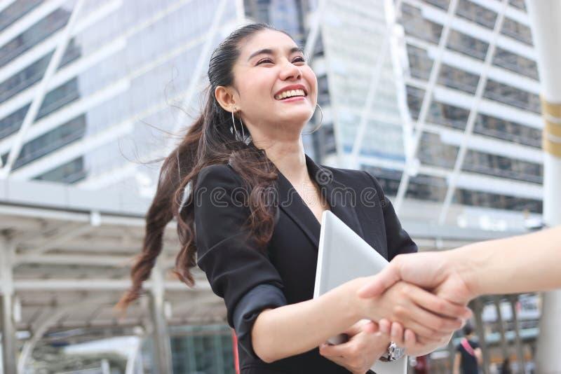 Успешная молодые азиатские бизнес-леди и человек тряся руки после дела партнерство рук принципиальной схемы различное соединяет г стоковые фото