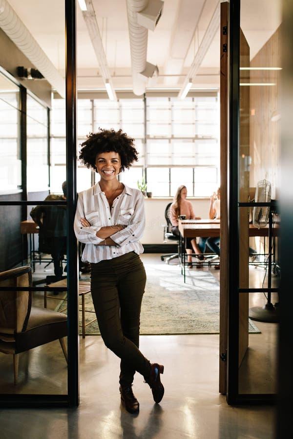Успешная молодая женщина полагаясь к входу офиса стоковое фото