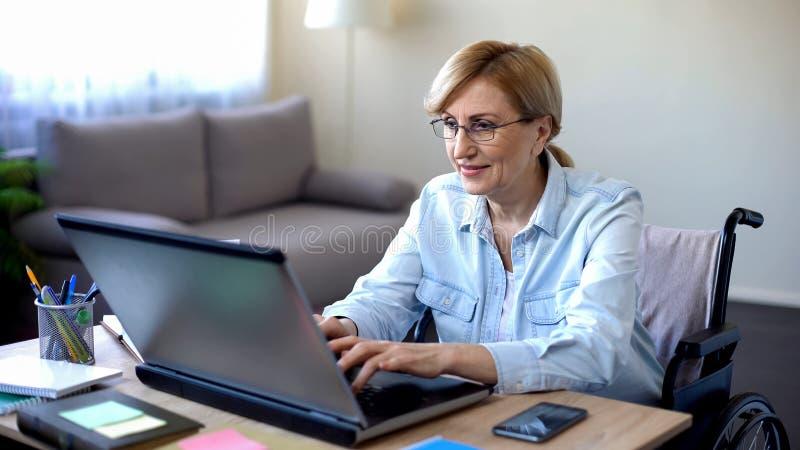 Успешная старшая женщина в кресло-коляске работая на компьтер-книжке, беседуя с клиентом стоковое изображение rf