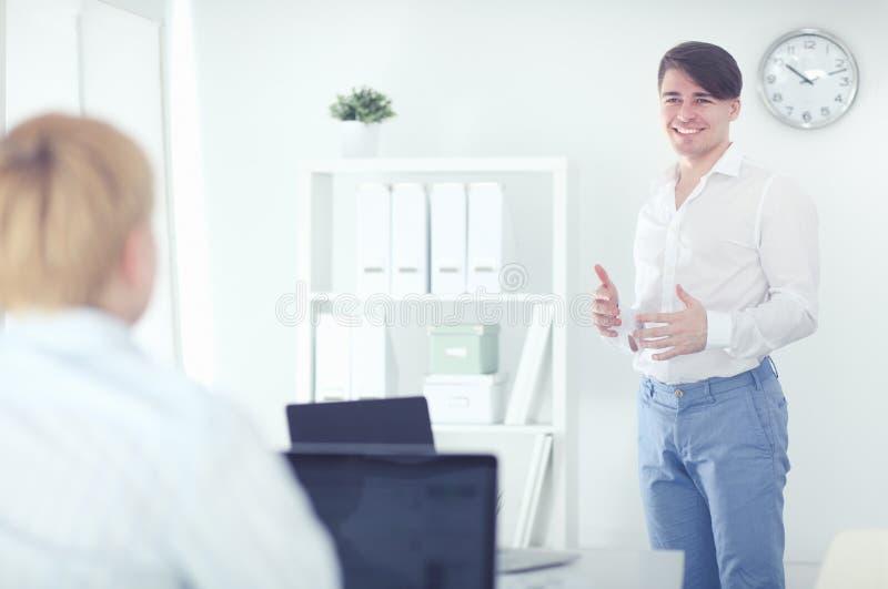 Успешное молодое положение бизнесмена в его офисе стоковое фото