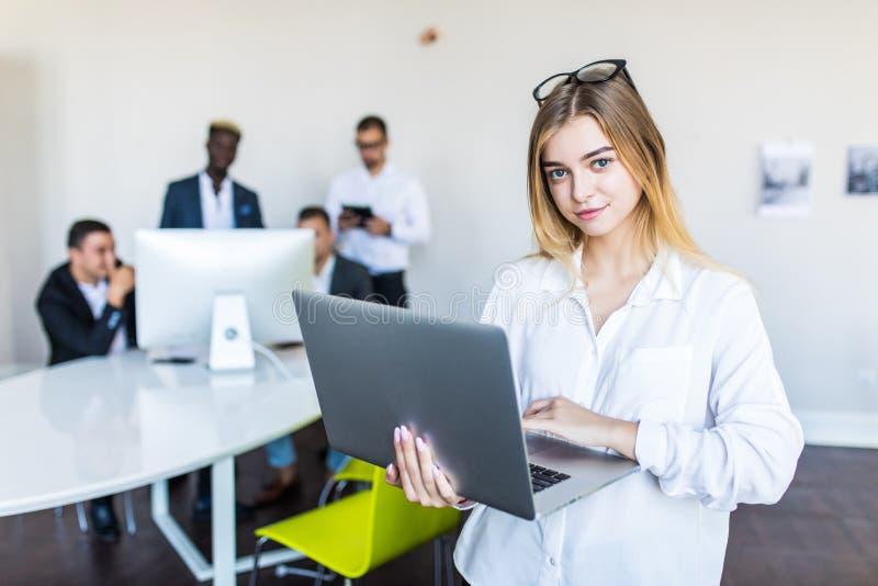 Успешное положение бизнес-леди с ноутбуком с ее штатом в предпосылке на современном ярком офисе стоковое изображение rf