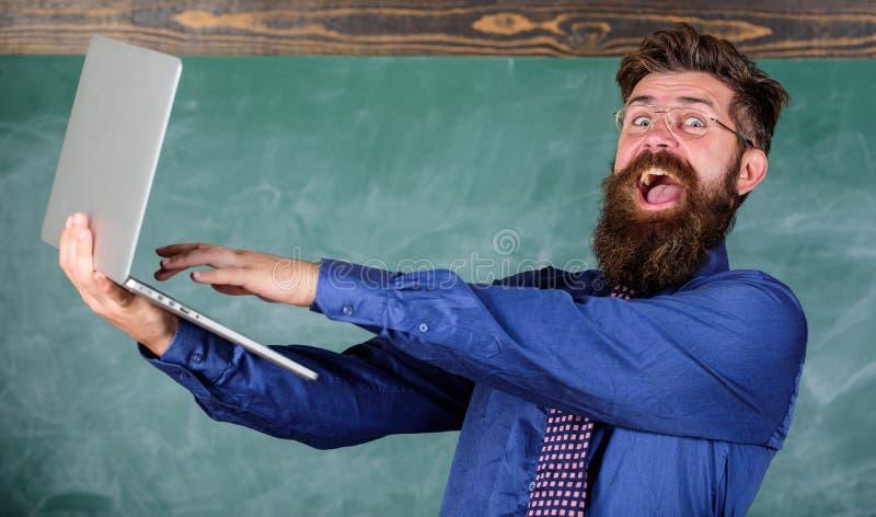 Успешное рассмотрение Человек учителя бородатый счастливый с современной компьтер-книжкой прошел испытанием онлайн предпосылку до стоковые изображения