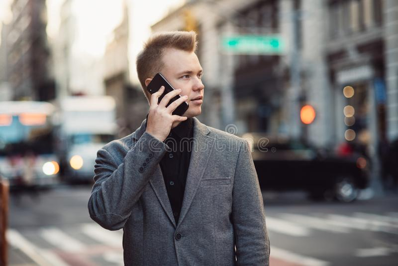 Успешные беседы бизнесмена по телефону на занятой улице города Нью-Йорка нося костюм стоковые фотографии rf