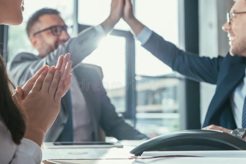 успешные бизнесмены давая высоко 5 во время встречи стоковые изображения
