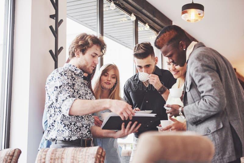 Успешные молодые бизнесмены говорящ и усмехающся во время перерыва на чашку кофе в офисе стоковые изображения