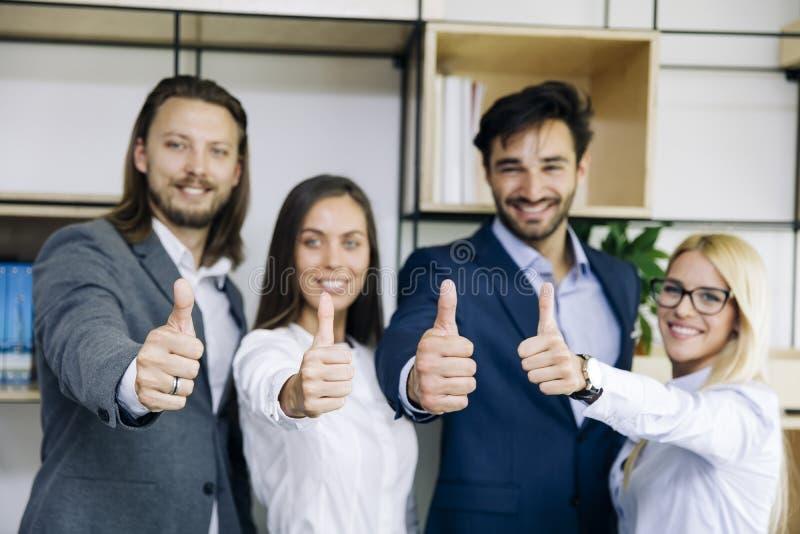 Успешные молодые бизнесмены показывая большие пальцы руки вверх по знаку стоковые изображения rf