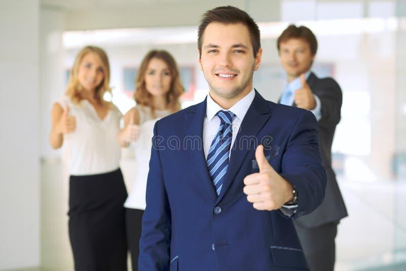 Успешные молодые бизнесмены показывая большие пальцы руки поднимают знак стоковая фотография rf
