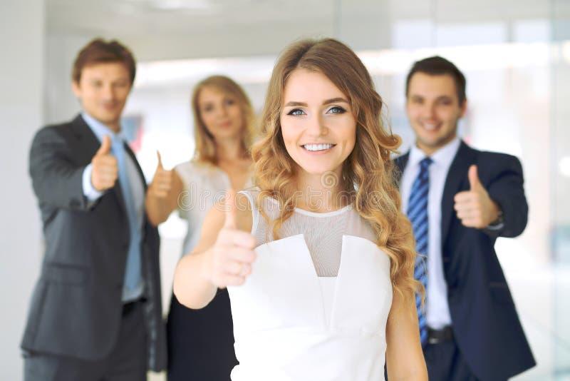 Успешные молодые бизнесмены показывая большие пальцы руки поднимают знак стоковое фото