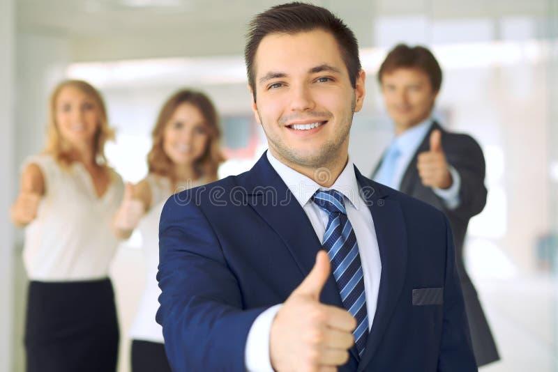Успешные молодые бизнесмены показывая большие пальцы руки поднимают знак пока стоящ в офисе более interier стоковое фото