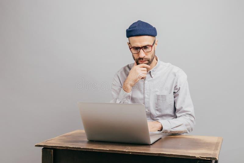 Успешные мужские дизайнерские клавиатуры на ноутбуке, проверяют базу данных, сидят на старой таблице, держат подбородок, носят оф стоковые фотографии rf