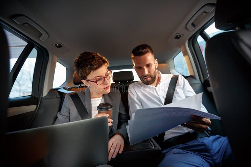 Успешные пары дела работая совместно в заднем сиденье автомобиля стоковые фото