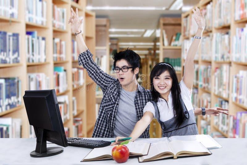 Успешные руки повышения студентов в библиотеке стоковые изображения rf