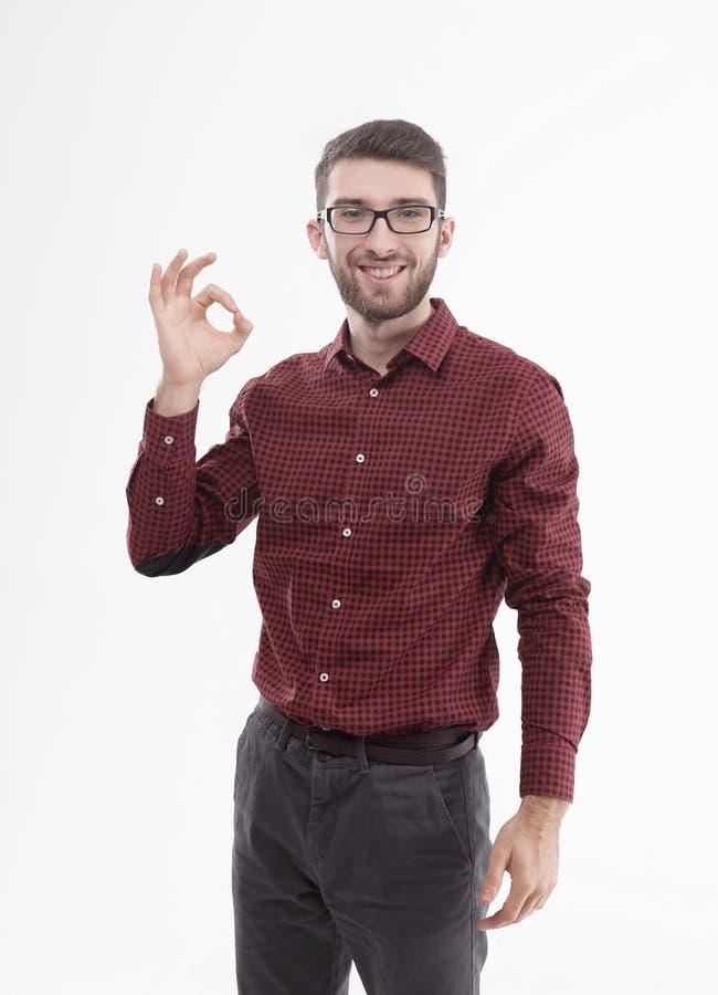 Успешные стекла молодого человека нося показывая ОДОБРЕННЫЙ знак Изолировано на белизне стоковое изображение rf