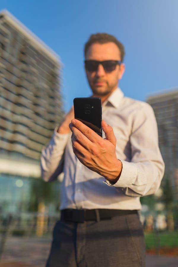 Успешные удерживание предпринимателя и мобильный телефон использования на улице стоковое фото