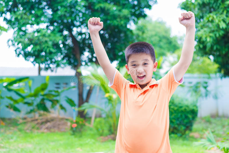 Успешный азиатский мальчик пробивая воздух с его кулаками в воздухе, smi стоковое изображение rf