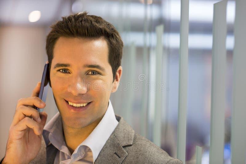 Успешный бизнесмен говоря на сотовом телефоне стоковое фото rf