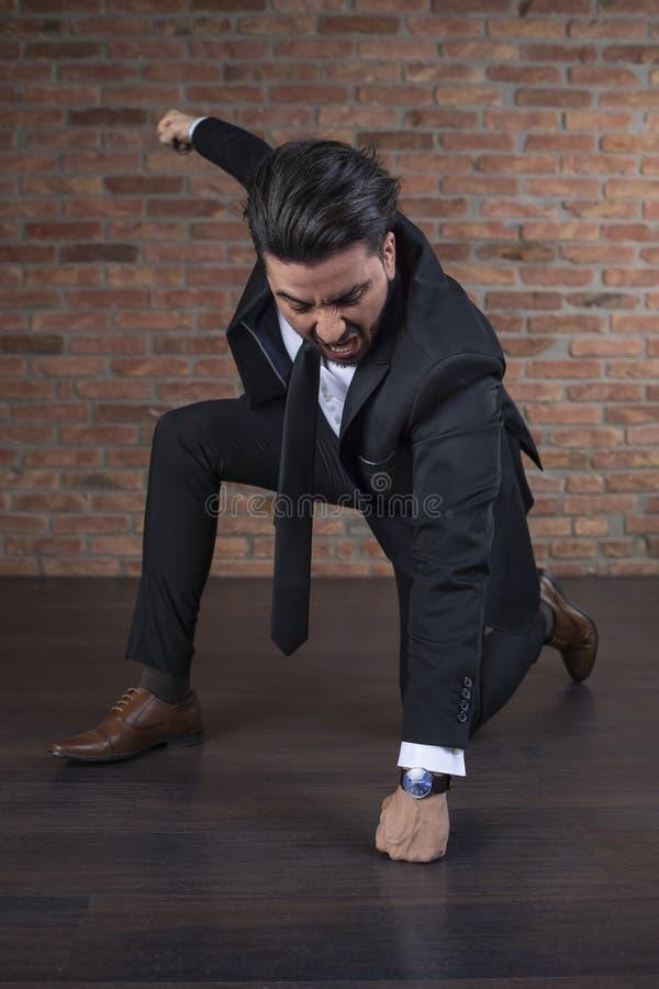 Успешный бизнесмен пробивая пол с его кулаком как супергерой стоковое фото rf