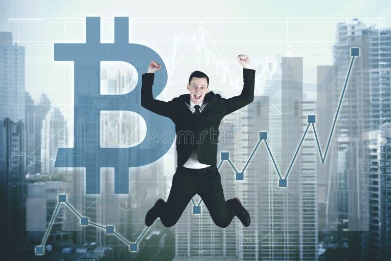 Успешный бизнесмен скача с символом bitcoin стоковые фото