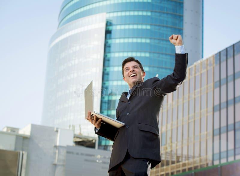 Успешный бизнесмен с знаком победы компьтер-книжки компьютера счастливым делая стоковое фото