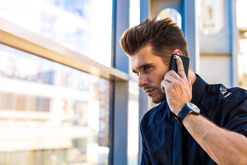 Успешный бородатый мужской главный исполнительный директор в официальном костюме зноня по телефону через телефон клетки стоковое фото