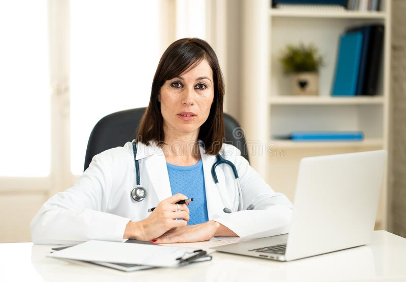 Успешный женский доктор работая в офисе больницы клиники усмехаясь и представляя для камеры стоковое изображение