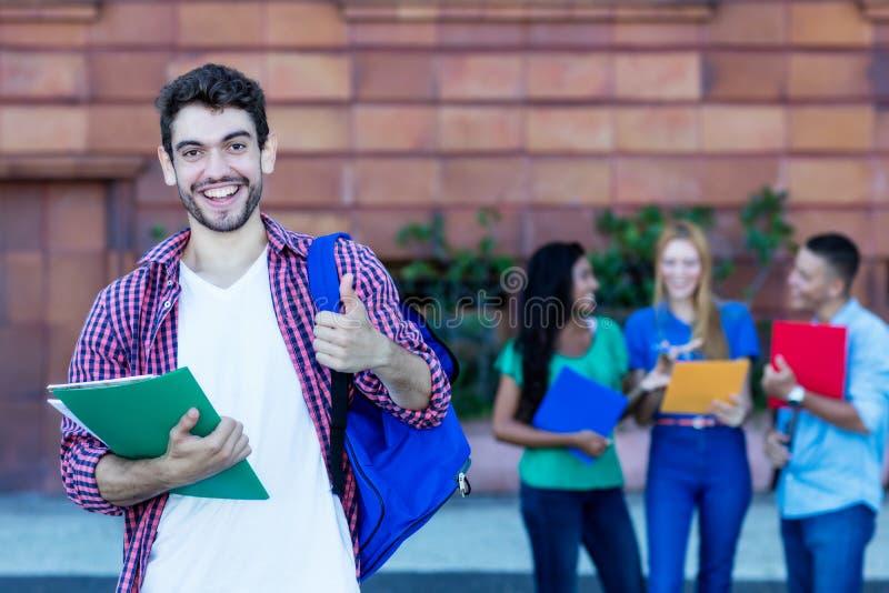 Успешный испанский студент с группой в составе студенты стоковые изображения