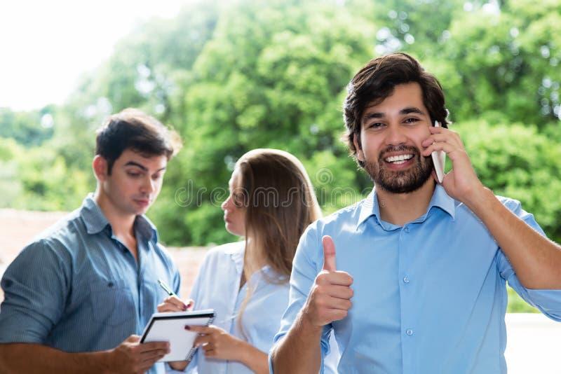 Успешный латино-американский бизнесмен на телефоне с другим busine стоковые изображения