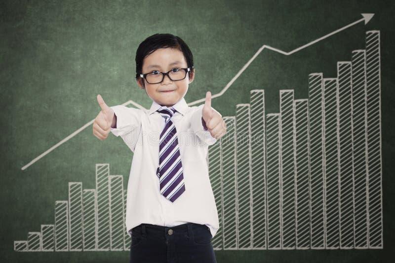 Успешный маленький бизнесмен над диаграммой дела стоковые фото