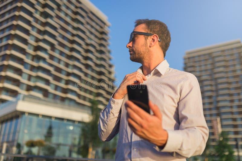Успешный мобильный телефон удерживания предпринимателя на улице стоковое изображение