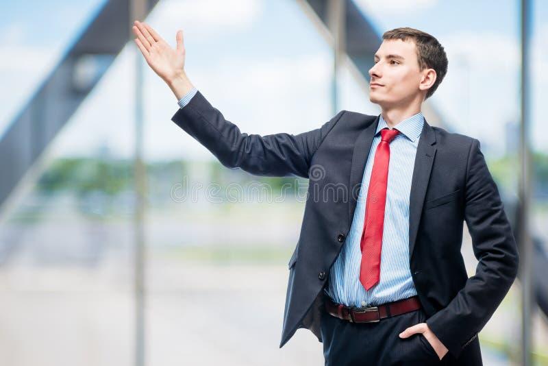 Успешный молодой босс показывать с руками стоковые изображения