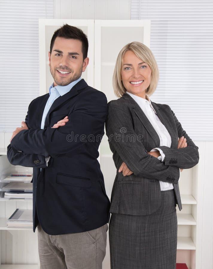 Успешный мужчина и женская команда дела: старшее и младшее mana стоковые изображения rf