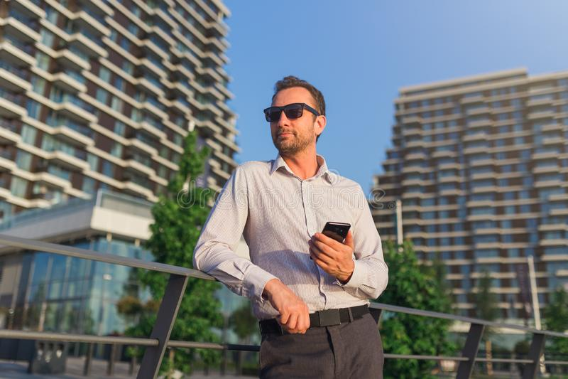 Успешный руководитель бизнеса используя смартфон outdoors Офисные здания на заднем плане стоковые изображения