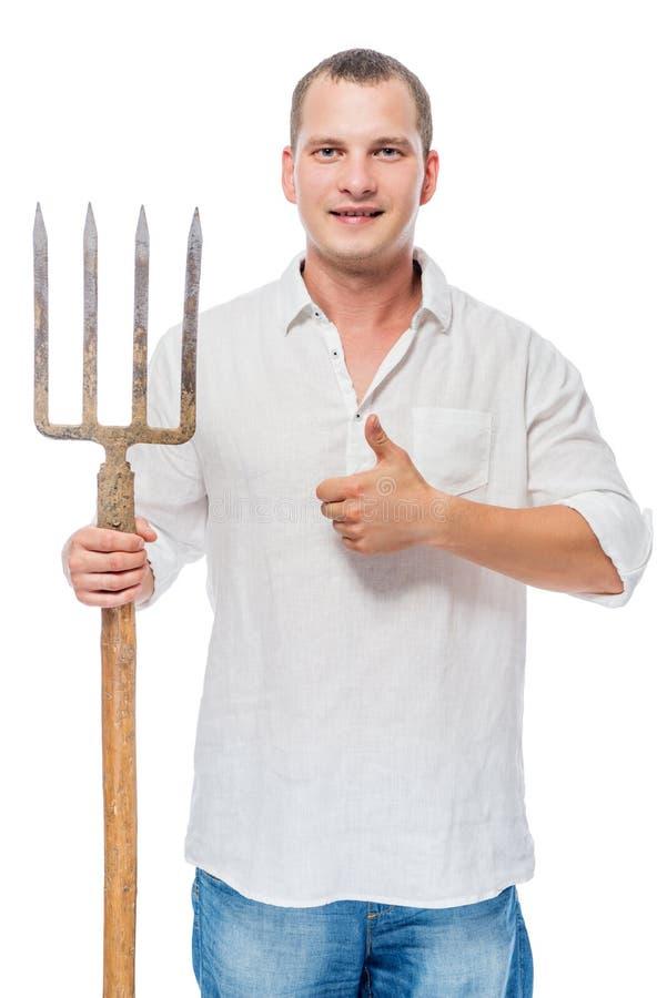 Успешный садовник с вилой на белом posin стоковые изображения