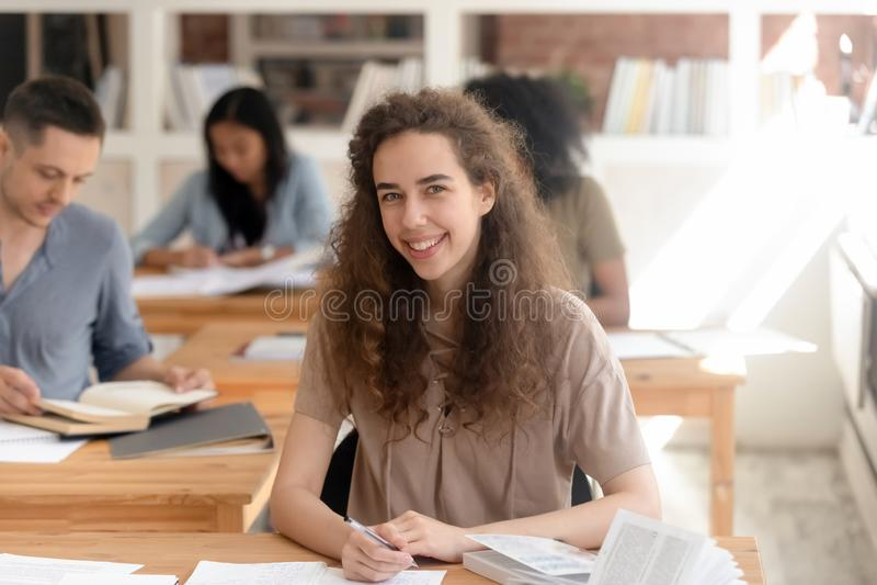 Успешный студент университета сидя на столе смотря камеру стоковые фото